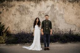 Les mariés devant un mur en pierre et lavandes, mariage style boho, design floral Lilas Wood fleuriste mariage en Provence alpes côte d'azur - Photographie Chris and Ruth.