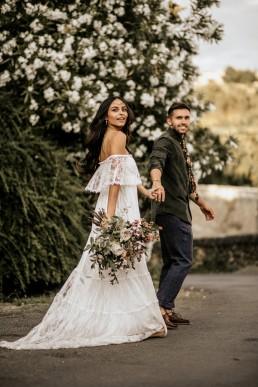 Les mariés qui marchent ensemble sur une route, mariage style boho, bouquet de mariée moderne, design floral Lilas Wood fleuriste mariage en Provence alpes côte d'azur - Photographie Chris and Ruth.
