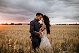 Les mariés dans un champs de blé, style boho, la mariée porte une robe moderne, design floral Lilas Wood fleuriste mariage en Provence alpes côte d'azur - Photographie Chris and Ruth.