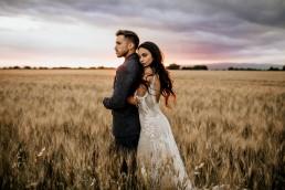Les mariés dans un champs de blé, style boho, design floral Lilas Wood fleuriste mariage en Provence alpes côte d'azur - Photographie Chris and Ruth.