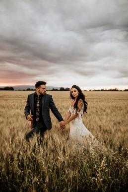 Les mariés dans un champs de blé, mariage style boho, design floral Lilas Wood fleuriste mariage en Provence alpes côte d'azur - Photographie Chris and Ruth.