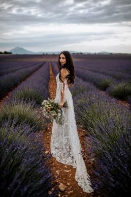 La mariée dans un champs de lavande, mariage style boho, elle porte un bouquet moderne, design floral Lilas Wood fleuriste mariage en Provence alpes côte d'azur - Photographie Chris and Ruth.