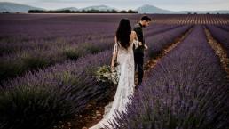 Les mariés dans un champs de lavande la mariée porte un bouquet moderne, mariage style boho, design floral Lilas Wood fleuriste mariage en Provence alpes côte d'azur - Photographie Chris and Ruth.