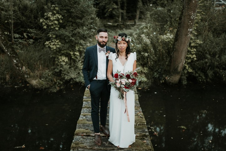 Les mariés sur un pont de bois, couronne de fleurs et bouquet de la mariée confectionnés par LILAS WOOD - Fleuriste Mariage Dijon & Bourgogne.
