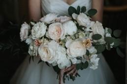 La mariée tenant son bouquet de la mariée confectionné par LILAS WOOD, Design Floral & Fleuriste Mariage Genève en Suisse - Photographe - Le château de Coudrée.